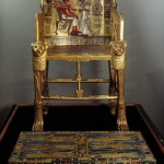 Built of multiple pieces of wood the entire chair has been covered  with either painted gilding or sheets of gold and inlaid with semiprecious stones and colored glass.On the back is an image of the king with the atef crown seated on a throne and his wife stands before him. Behind the queen is a broad collar shown as if in a bird's eye view. The arms of the throne are composed of winged cobras wearing the double crown of a united Egypt. above the footstool.
